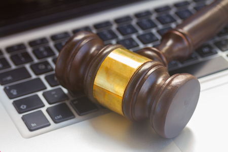 judgement: Wooden law gawel on laptop keyboard close up, judgement concept