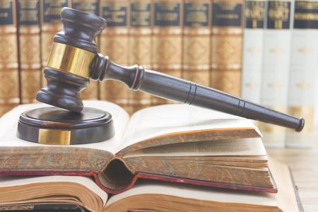 libros abiertos: Martillo de madera de la Ley en los libros abiertos con una fila de libros de derecho