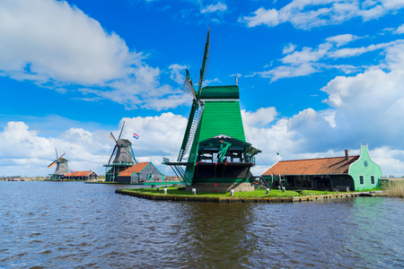 water mill: Dutch scenery with windmills over river of Zaanse Schans at summer day, Netherlands Stock Photo