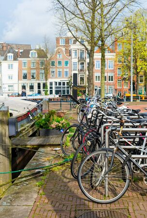 Row of bicycles standing next to canal in Amsterdam at spring, Netherlands Stock Photo
