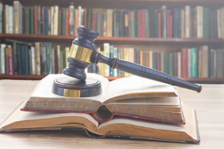 Wooden Law Gavel on open books with a row of law books in library Stock Photo
