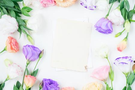 Marco de flores de eustoma rosa, blanco y violeta y notas de papel envejecido en blanco Foto de archivo - 67390516