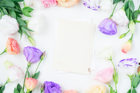 Pink, white and violet eustoma flowers frame and blank aged paper notes