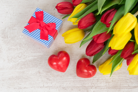 fresh yellow and red tulips with gift box and hearts for valentines day Stock Photo