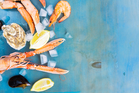 Fresh seafood border with ice, copy space on blue background