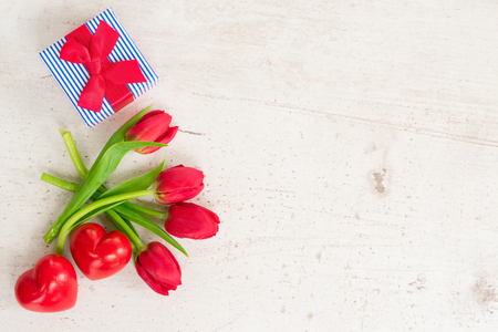 fresh red tulips with two hearts and gift box for valentines day, top view flat lay