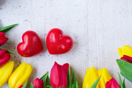 yellow and red tulips with with two loving hearts for valentines day, top view close up Stock Photo