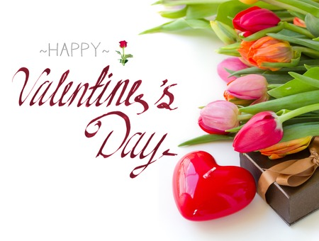 valentines day mother s: tulips with gift box and red heart candle on white table with happy valentines day greeting