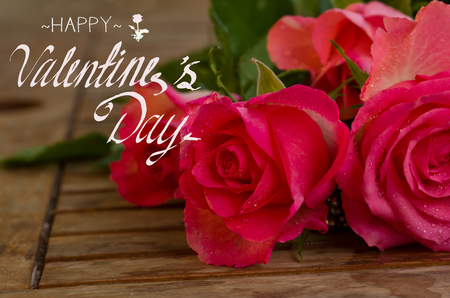 bouquet of pink roses in water droplets on wooden table with happy valentines day greeting Stock Photo