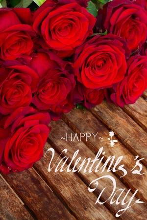 valentines day mother s: dark red fresh roses laying on wooden table with happy valentines day greetings Stock Photo