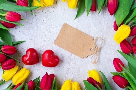 fresh yellow and red tulip flowers with with two hearts and empty paper note flat layed frame for valentines day Stock Photo