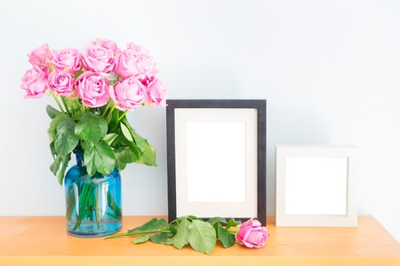 Violet fresh roses with two empty photo frames on wooden shelf Фото со стока