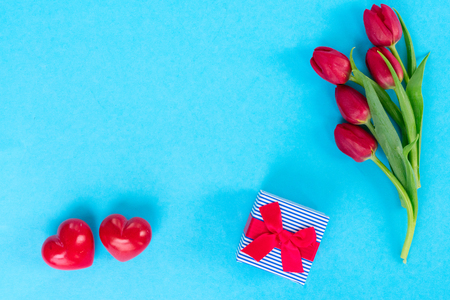 posy of red tulips with two hearts ans gift on bright blue background Stock Photo