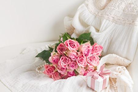 Vestido de mujer y joyas con ramo de rosas freah y caja de regalo en silla Foto de archivo - 71829304