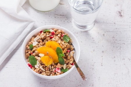 Healthy breakfast - plate of granola with orange slices, mint and seeds Stock Photo