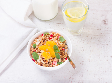Healthy breakfast - white plate of granola with orange slices, mint and seeds Stock Photo