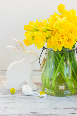 Easter eggs hunt - white porcelane rabbit with eggs and daffodils bouquet