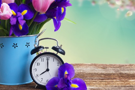 Spring time concept - retro alarm clock with flowers copy space on blue bokeh background