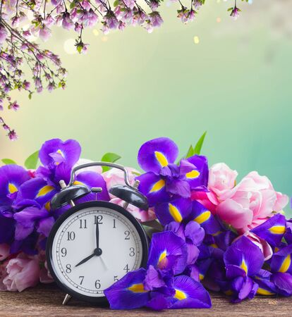 Spring time concept - retro alarm clock with fresh flowers, spring garden in background