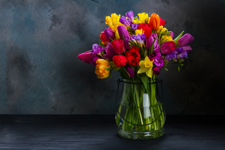 bouquet of bright spring flowers in vase on black background