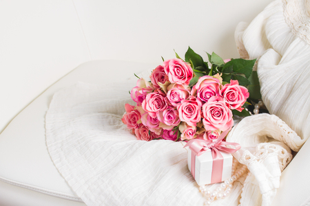 Female dress and jewellery with freah roses bouquet and gift box on chair, place for copy space Stock Photo