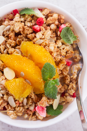 Healthy breakfast - plate of granola with orange slices, mint and seeds close up Stock Photo