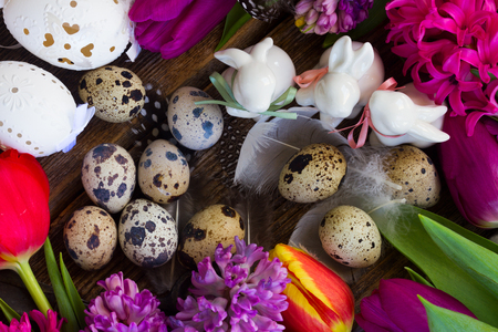quail: Spring fresh flowers with easter eggs and three white pocelane rabbits close up Foto de archivo