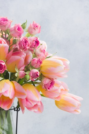 fresh pink and yellow tulips and roses close up