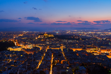 panoramic cityscape of Athens with Acorpolis hill and sea at night, Greece