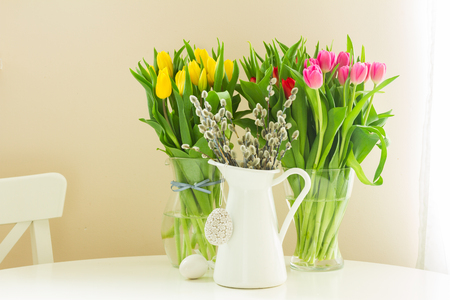 fresh yellow and violet tulips and willow catkins in pot with easter eggs