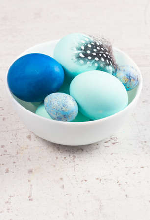 huevos de codorniz: Plate with painted blue eggs on aged wooden table desktop Foto de archivo