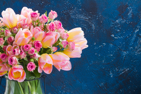 fresh pink and yellow tulips and roses close up on blue background