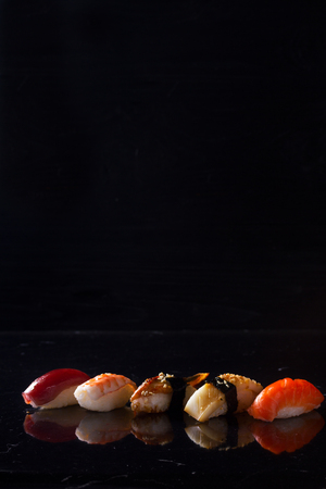 Japanese sushi dish on black background with copy space