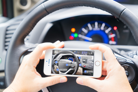 smart car concept - driving wheel and hands holding phone with