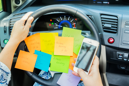 To do list in a car on driving wheel and hand holding phone - busy day concept