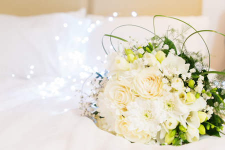 white fresh roses, freesia and mum flowers bouquet on bed, hygge style