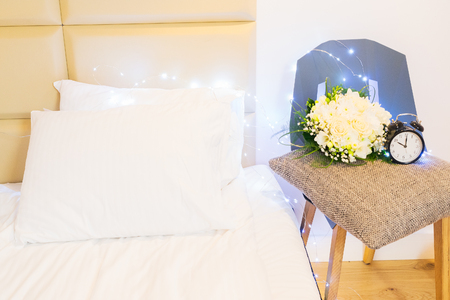 hotel bedroom: bedroom interior closeup - night table with flowers, hygge lifestyle