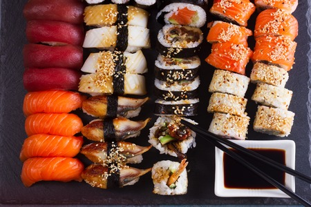 Japanese sushi big set with wooden black chopsticks, top view