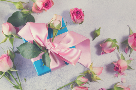 pink satin: Gift blue box with pink satin bow and rose flowers close up, retro toned