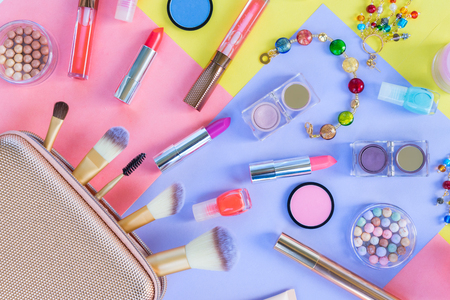 Colorful make up products with golden pursue close up meterial design flat lay scene Stock Photo
