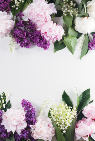 Floral borders of fresh flowers - lilac, peonies and lilly of the walley flowers on white background with copy space