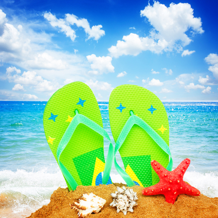 pair of green sandals and starfish in sand by sea side, retro toned Stock Photo