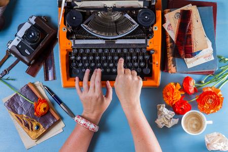 Workspace with someone hands typing on orange vintage typewriter on blue background Stock Photo