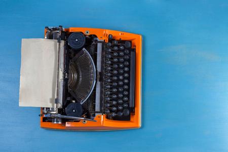 Workspace with orange vintage typewriter on blue background Stock Photo