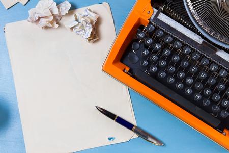 オレンジ色のヴィンテージ タイプライターと青色の背景の空の紙のワークスペース