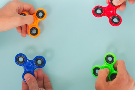 trendy fidget spinners - styled flat lay scene with hands holding colorful generic design spinners, copy space on blue background Stock Photo