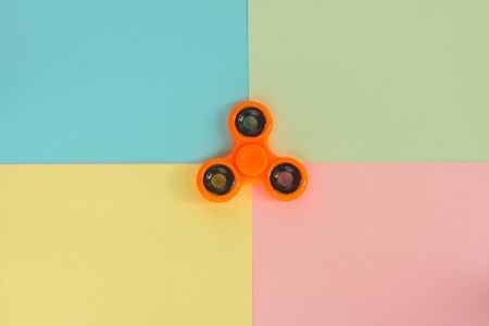 trendy fidget spinners - styled pop art flat lay scene with generic design orange spinner Stock Photo