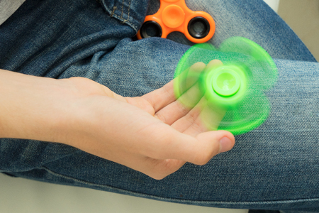 banned: trendy fidget spinner - person holding spinning green fidget spinner in hand, close up view Stock Photo