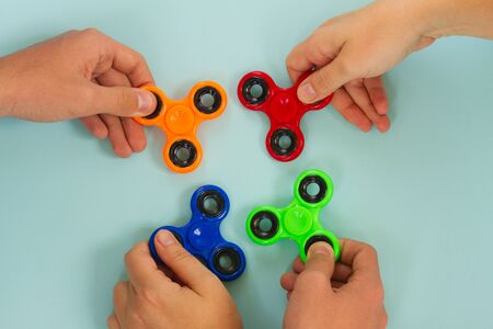 trendy fidget spinners - styled flat lay scene with hands holding colorful generic design spinners on blue