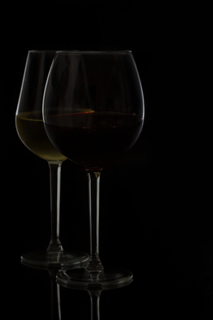 abstract liquor: Wine glasses on black - two glasses of red and white wine Stock Photo